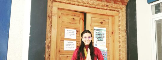 """The author is doing a Namaste pose in front of her office's main gate. She is wearing a Chuba. The board above her says. """"Department of Education, Central Tibetan Administration"""" which is the name of her host organization."""