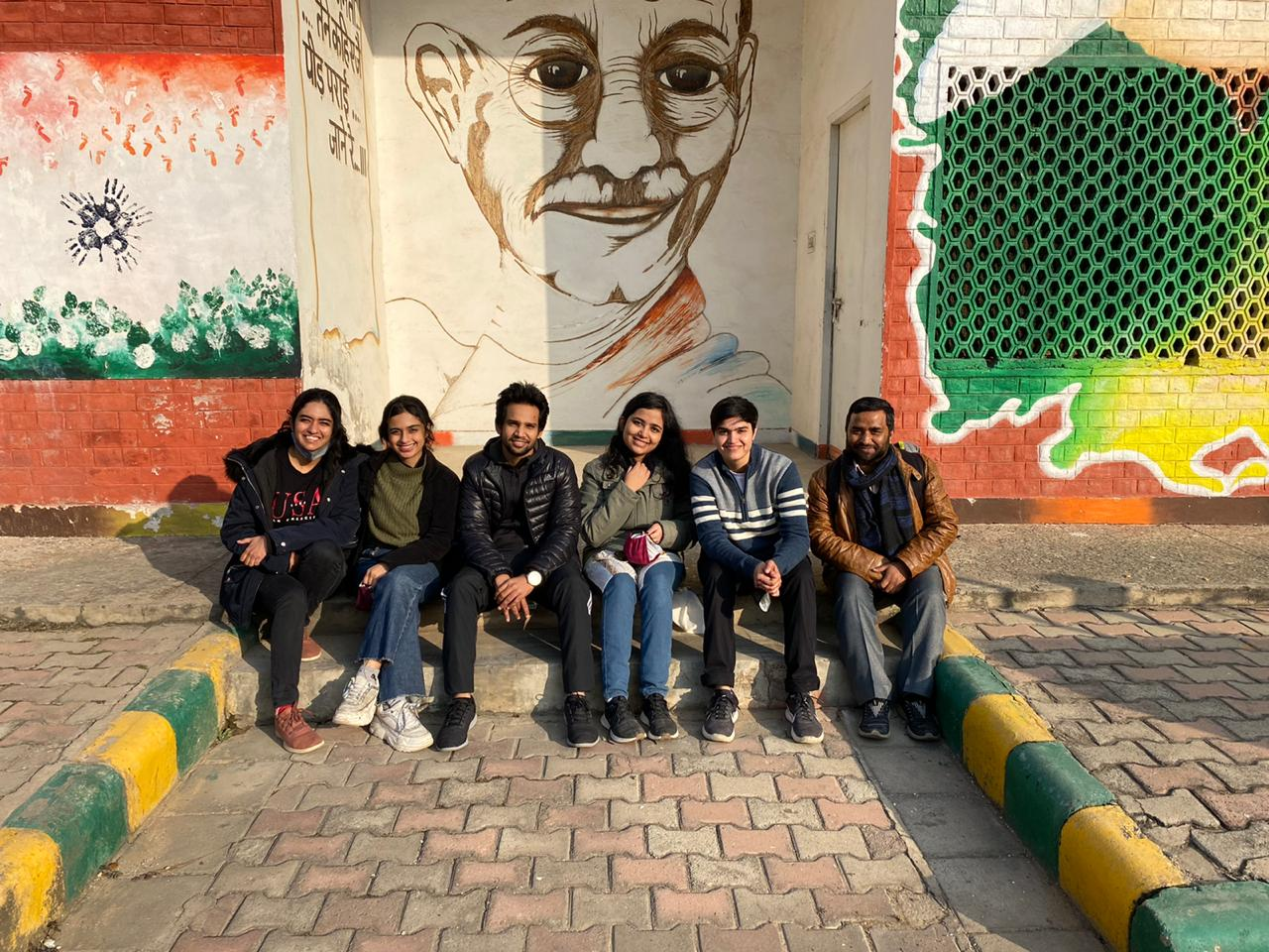 Shivranjani with her colleagues in front of a Gandhi-ji mural near the prison entrance.