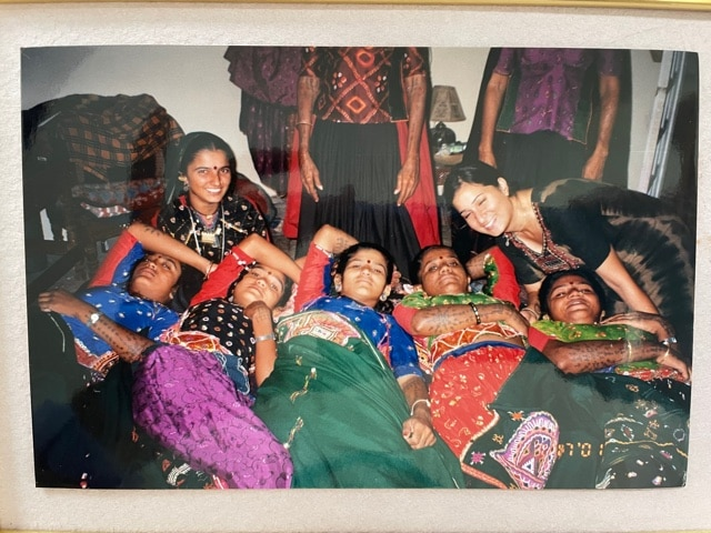 Meenakshi leaning into six women artisans lounging on the floor, smiling.