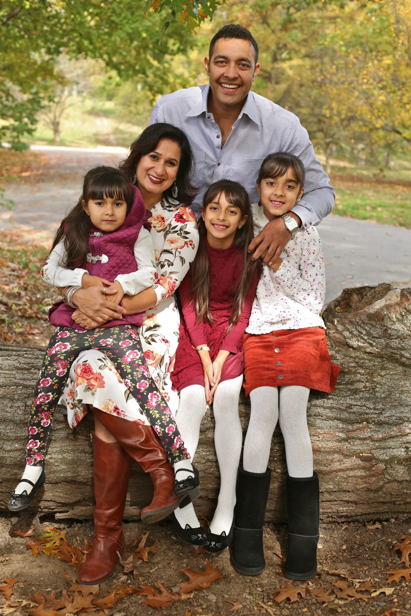 Meenakshi posing with her husband and three young girls in a park, sitting on a tree trunk, with lush green foliage in the background.