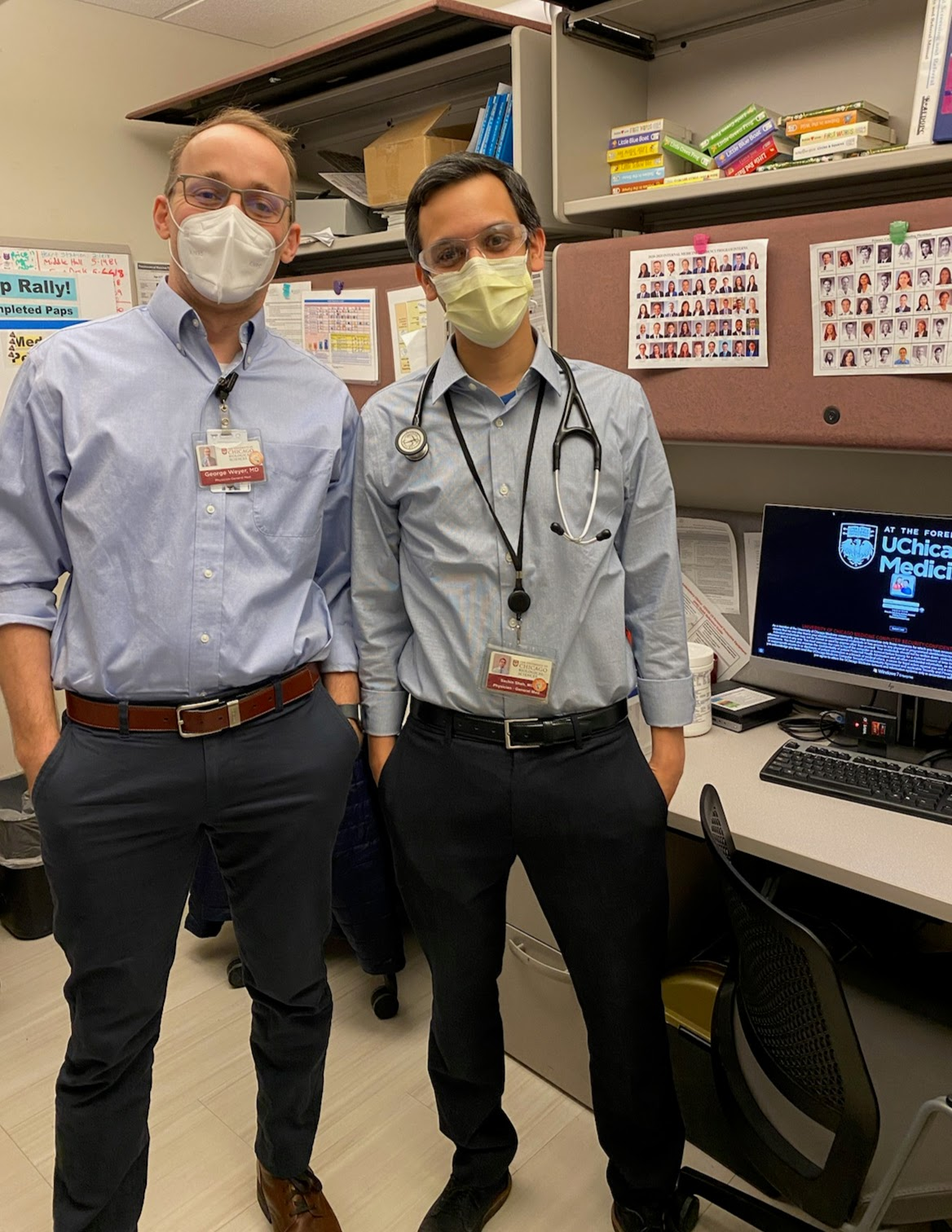 Sachin standing with his co-worker in an office, both wearing masks and glasses. A stethoscope casually wrapped around Sachin's neck.