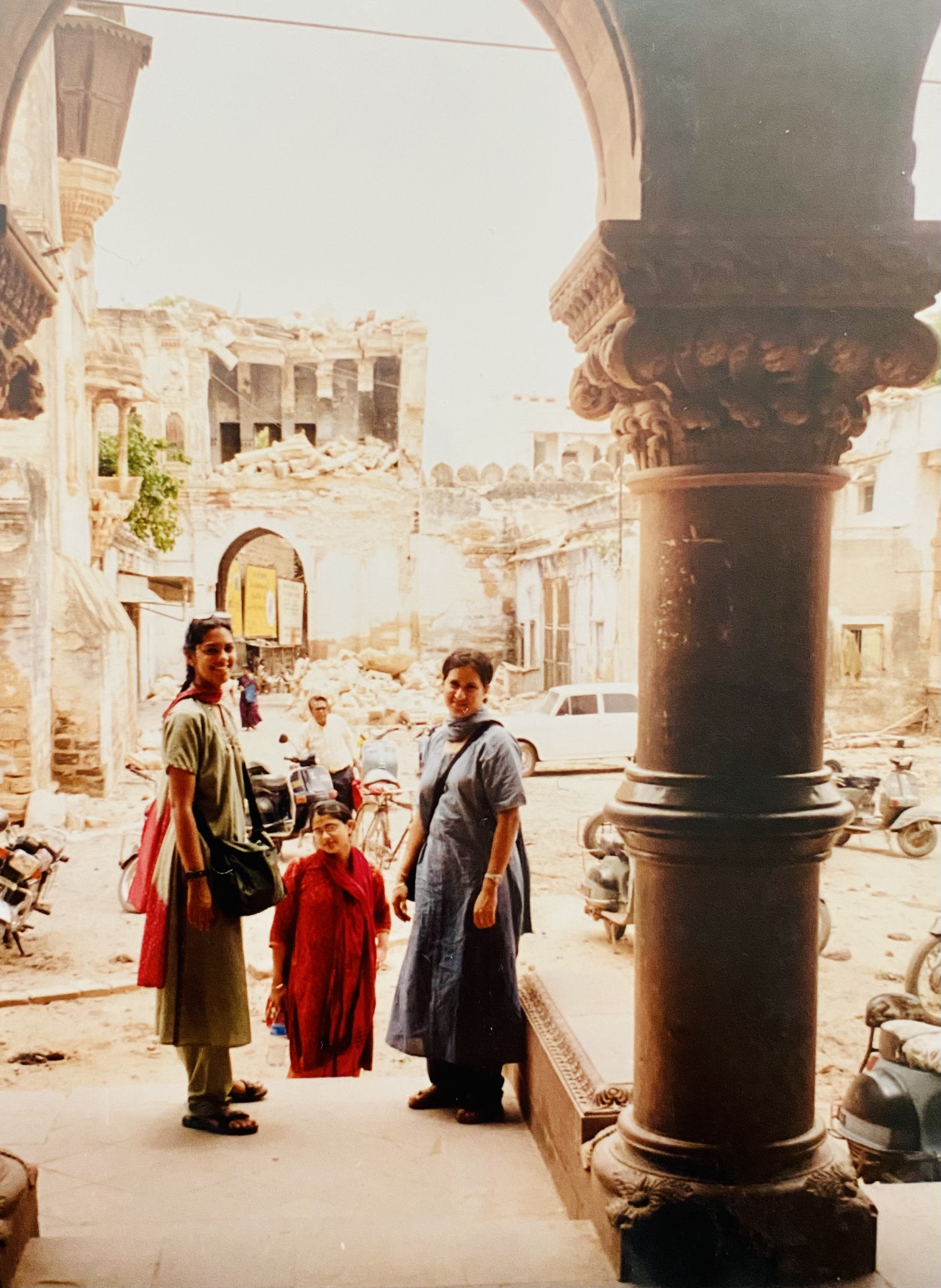 Meenakshi, Shruti and Tanvi standing in front of the ruins of buildings.
