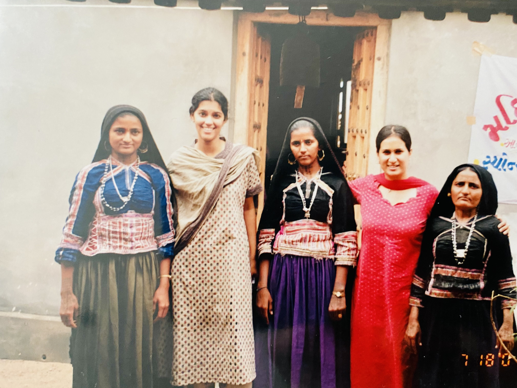 Tanvi and Meenakshi pose with three local women, all clad in colorful traditional outfits with embroidery.