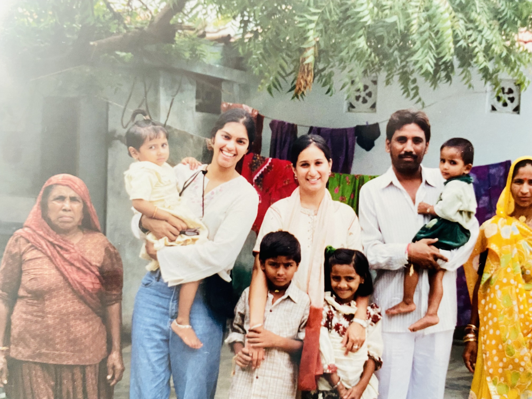 Tanvi holding a young girl in her arms, standing next to Meenakshi, who embraces two children, and left and right of them, adult members of the family with another child.
