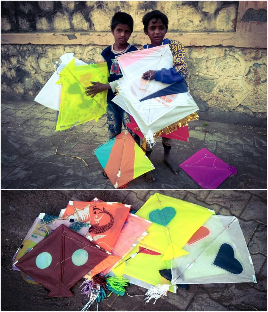 Two migrant children displaying their collection of colorful kites which they have gathered from the roadside