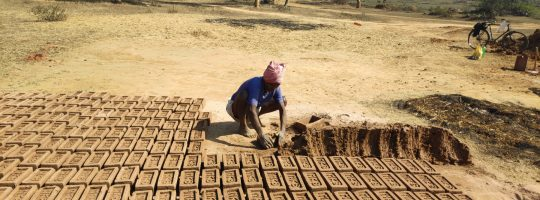 A man moulding sand into brick as part of his livelihood.