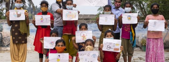 Group of girls with Anushri showing their drawings.
